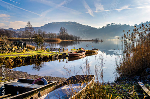 Fotografie, Obraz Boats at rest on Grasmere water by the village in the centre of the Lake District Cumbria
