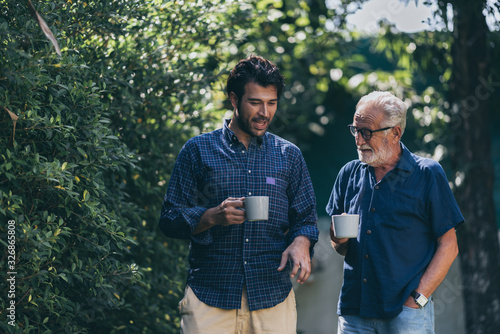 Canvas Print An adult hipster son and senior father at home, talking.