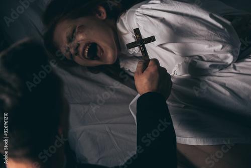 Fotografering exorcist holding cross over demonic yelling girl in bed