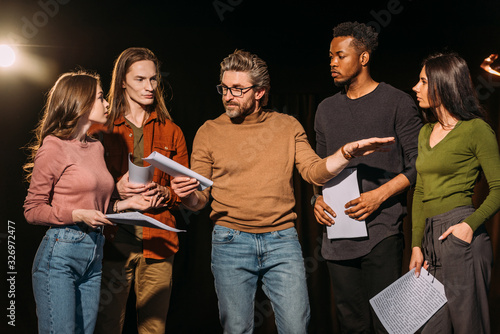 Canvas multiethnic actors and actresses rehearsing with theater director on stage