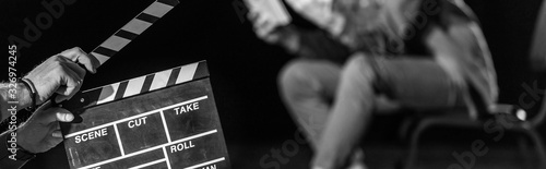 Fotografía panoramic shot of actor with clapperboard in front, isolated on black, black and