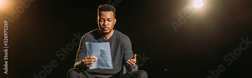 Foto panoramic shot of african american actor holding scenario on stage during rehear