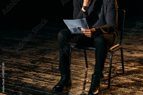 Photographie cropped view of african american actor holding scenario on stage during rehearse