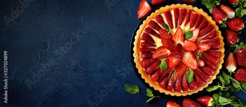 Fotografia Delicious fresh strawberry tart on trendy dark blue background