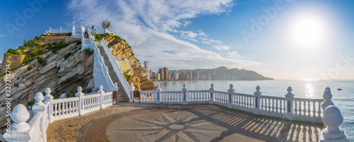 """Рanoramic seascape view on beach and skyscrapers from observation deck so-called """"Balcon del Mediterraneo"""" with white balustrade and makeshift compass on the floor. Costa Blanca. Benidorm, Spain."""