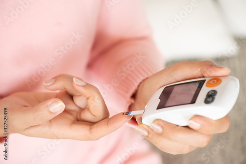 Fotomural Close up of woman hands checking blood sugar level by Glucose meter for diabetes tester using as Medicine, glycemia, healthcare and medical concept