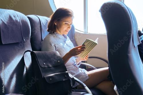 Canvastavla Adult female passenger sitting on armchair near window in ferry cabin