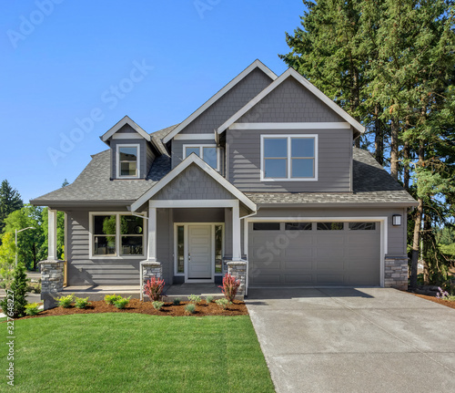 Fotografia Suburban home exterior on bright sunny day, with large yard and covered porch