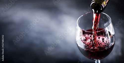 Fototapete Pouring glass of red wine from a bottle in wide banner shape or copy space for text..