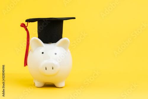 Murais de parede White piggy bank wearing graduation cap on yellow background with copy space, ed