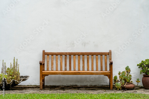 Fotografering Wooden bench front of a white wall