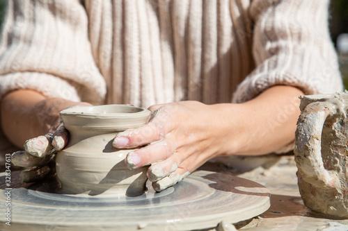 Vászonkép Womans hands working of ceramics on potter wheel closeup