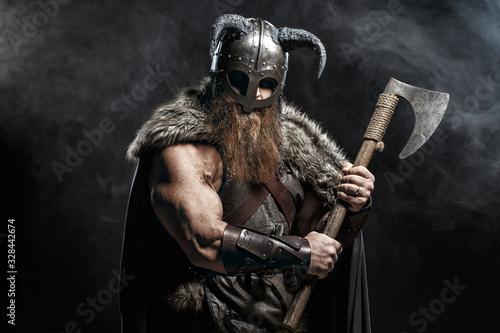 Obraz na plátně Medieval warrior berserk Viking with axes attacks enemy