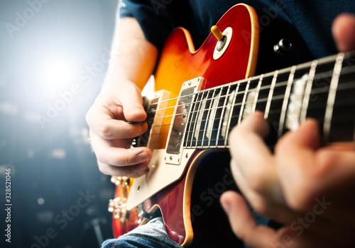 Fototapeta man playing on guitar close up view