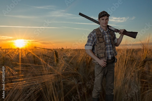 Fototapeta Male hunter with a rifle on a natural background