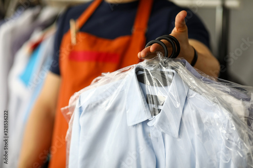 Fotografia, Obraz Clothes dry cleaning service worker returning shirts to customer