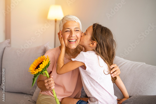 Fotografia, Obraz Little preschool granddaughter kissing happy older grandma on cheek giving viole