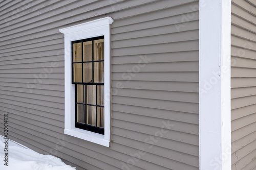 Photo The exterior wall of a grey colored building made of narrow wooden clapboard with a large drift of snow
