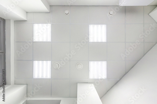 Photo cassette suspended ceiling with square halogen spots lamps and drywall construction in empty room in apartment or house