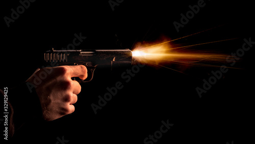 Fotografia The hand presses the trigger of the gun and the flame from the shot escapes from