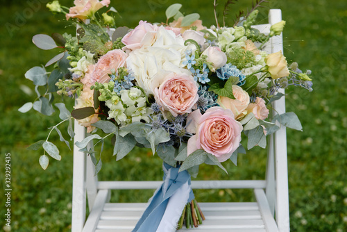 Fototapeta Close up of bridal bouquet of pink roses, blue flowers and greenery on white wood chair outdoors, copy space