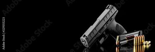 Fotografia Black modern gun and ammunition for it on adark  background