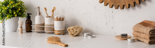 Panoramic view of shelf with hygiene objects and beauty products with flowerpot in bathroom, zero waste concept