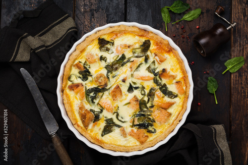 Fotografia Homemade quiche tart with red fish and spinach on dark wooden background