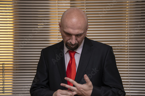Fotografia A man in a suit and tie removes a ring from his finger, or puts on an engagement ring against the background of blinds