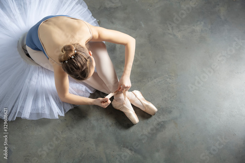 Leinwand Poster Top view at ballet dancer tying slippers around her ankle