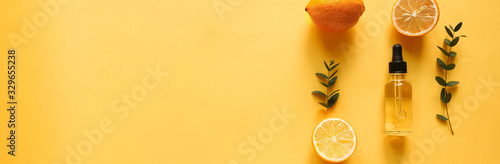 bright flatlay composition with oil, citrus and eucalyptus. on yellow background. Concept beauty natural vitamin cosmetic product, skin care, copyspace, top view, banner