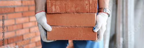 Valokuva Gloved builder manually carries brick construction