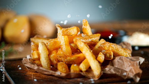 Obraz na płótnie Freeze Motion Shot of Falling Fresh French Fries on Wooden Table and Adding Salt