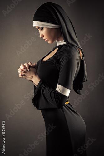 young nun in a black robe prays Fototapeta