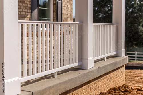 Fotomural Covered porch with brick siding, pre cut and pre mitered white columns, column w