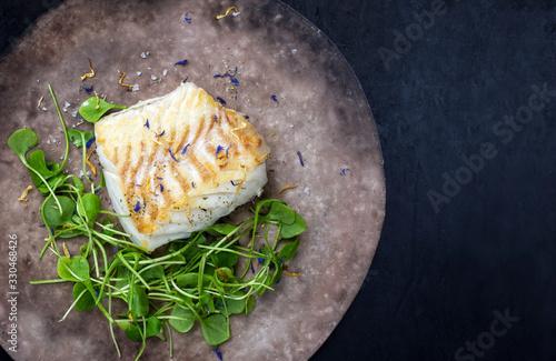 Photo Gourmet fried European skrei cod fish filet with purslane lettuce and herbs as t