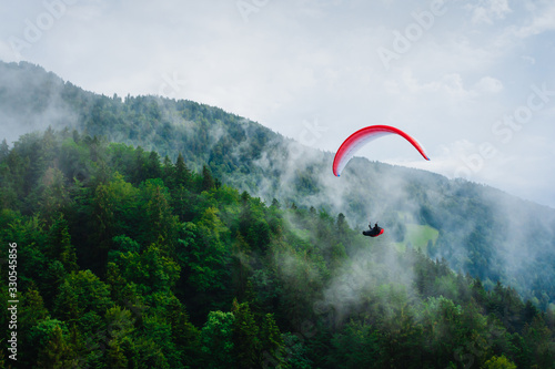 Fototapeta Paragliding in Austria. Alps. Clouds on the background.