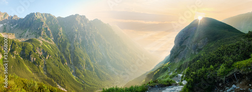 Fotografie, Obraz Deep mountain valley in morning sunlight, panoramic view