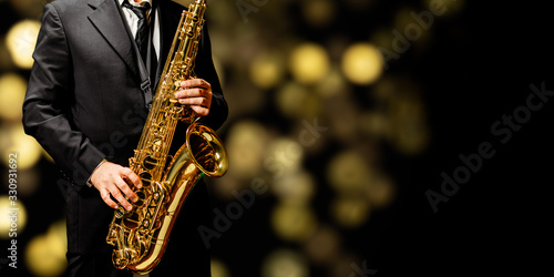 Fotografie, Obraz Playin' sax isolated at the left border of a black background