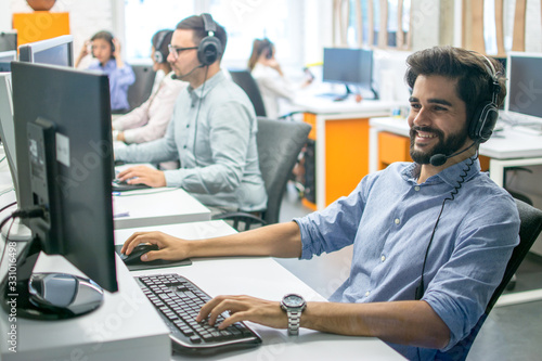 Fotomural Customer support operators working together in call center