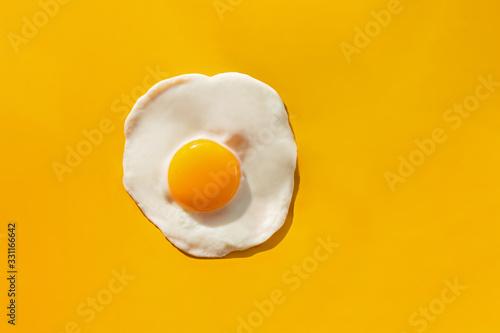 Fried egg on yellow background Fototapeta