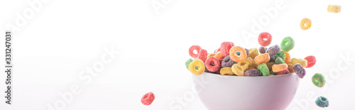 Photo bright multicolored breakfast cereal falling in bowl isolated on white, panorami
