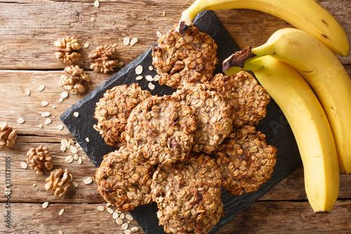 Obraz na płótnie Homemade low-calorie banana cookies with oatmeal and walnuts close-up on a slate board