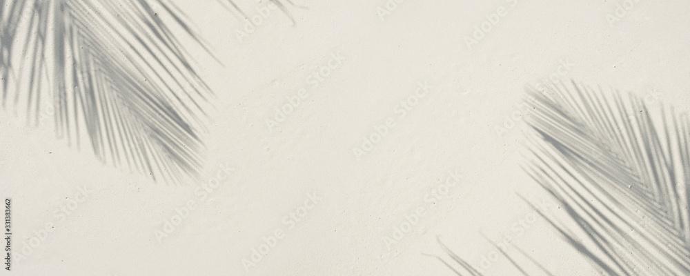 Palm leaf shadows on tropical sandy beach abstract background