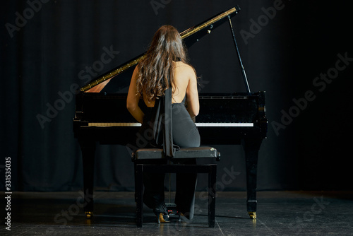 A woman playing a grand piano on a stage Fototapete