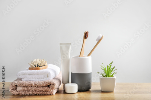 Foto Wooden toothbrushes, dentifrices, bath towels and hairbrush on wooden surface on