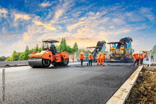 Obraz na plátně Construction site is laying new asphalt road pavement,road construction workers and road construction machinery scene