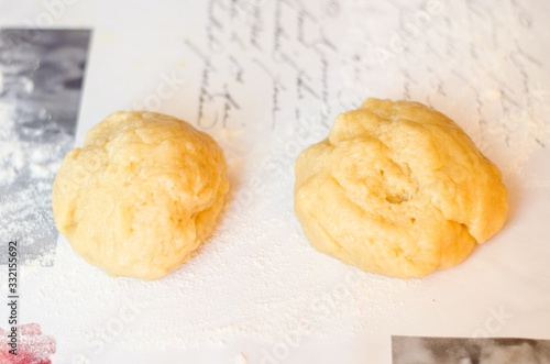 Fényképezés A ball of sweet pastry for shortcake lies on a table sprinkled with flour