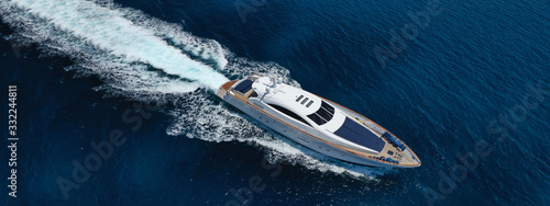 Aerial drone top down photo of luxury yacht with wooden deck anchored in open ocean sea