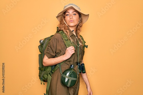 Obraz na płótnie Young blonde explorer woman with blue eyes hiking wearing backpack and water canteen looking at the camera blowing a kiss on air being lovely and sexy